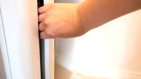 lids : A hand opens the door to the dryer, places a fabric softening sheet inside