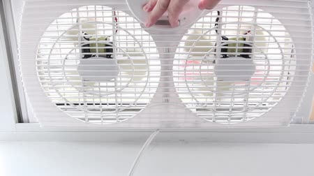 číslo : A hand reaches out to turn off the switch that is controlling a dual sided white window fan.