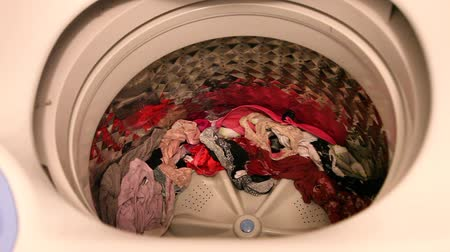 The lid of a washing machine is closed when a hand opens it, showing clean wet laundry Stok Video