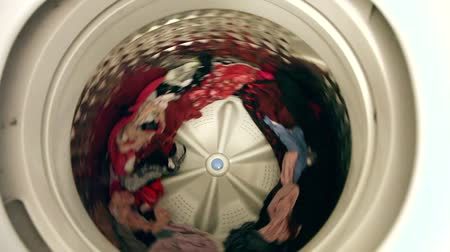 compleição : A clean load of clothes in a washing machine comes slowly to a stop from spinning.