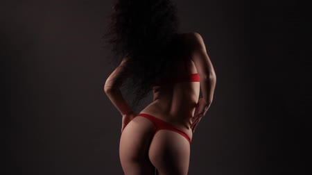 эротический : Sexy brunette woman in red lingerie dancing in the dark. Studio. Black background