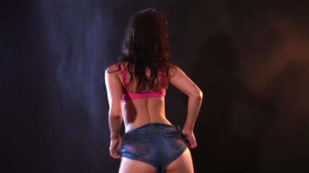 болваны : Sexy wet brunette in jeans and bra dancing on black background. Splashing water on background. Стоковые видеозаписи