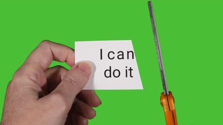 olasılık : Model holding card in front of green screen, then cutting card to change text from I cant do it to I can do it. Stok Video