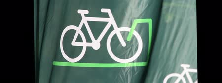 рекламный : A green background banner flag with an icon of a bicycle on it waving in the wind quite strongly.
