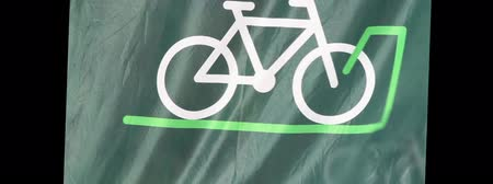 fitnes : A green background banner flag with an icon of a bicycle on it waving in the wind.