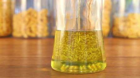 olive colored : A glass jar fills up with golden colored olive oil that comes down in a steady stream with random splashes. The jar sits on a wooden table in front of other jars of pasta.   Stock Footage