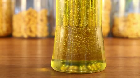 olivový olej : Bubbles inside a golden colored jar of olive oil change direction from downward to floating upwards.