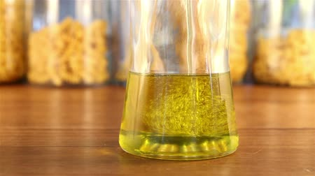 olive colored : A glass jar fills up with golden colored olive oil on a wooden table in front of jars of pasta.  Hundreds of air bubbles are created in the process. Stock Footage