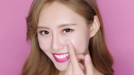 hydratují : beauty makeup woman smile and applying moisturizer cream on her pretty face Dostupné videozáznamy