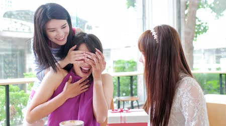 bestie : happy women friends feel surprise with gift in restaurant Stock Footage