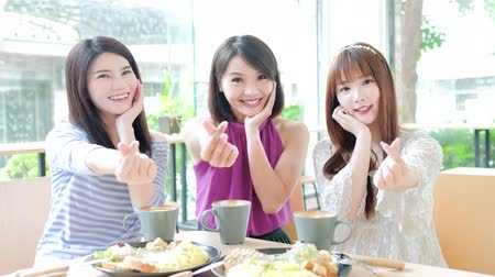 bestie : happy women friends show heart gesture in restaurant Stock Footage