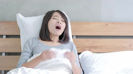 cold : Sick Woman sneezing into Tissue on the bed