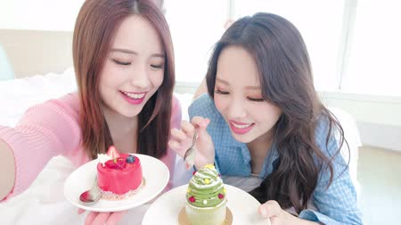 bestie : two beauty woman selfie happily and eat cake on the bed