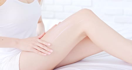 лицевой : beauty woman use cream with her leg at home Стоковые видеозаписи