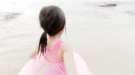 lifebuoy : cute girl wear lifebuoy and playing happily on the beach