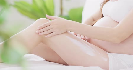 спальня : clsoe up of moisturizing cream on pregnant woman leg Стоковые видеозаписи