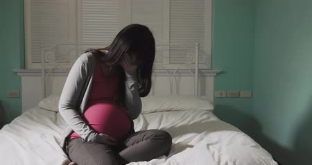 bekleyen : pregnant women sit on the bed and feel depression at home Stok Video
