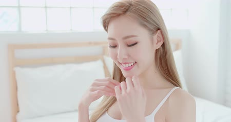 probudit se : skincare woman touch face on the bed at home Dostupné videozáznamy