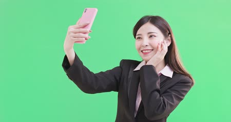photograph : businesswoman selfie happily on the green background Stock Footage