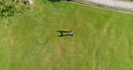 unmanned aircraft : aerial view of couple walking on the grass
