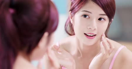 bochecha : beauty woman look mirror and touch her cheek in the bathroom