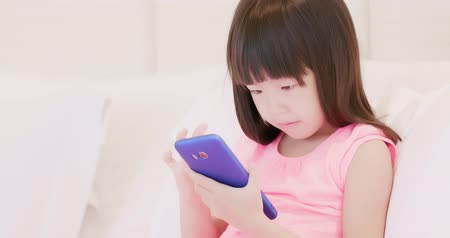 opieka : cute girl play phone and sit on the bed