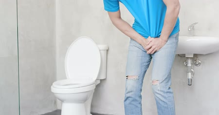 acil : man with urine urgency in the toilet Stok Video