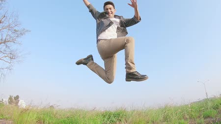 zöld fű : slow motion of man feel excited and jump on the grass Stock mozgókép