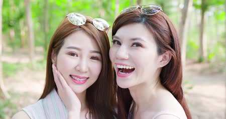 tynk : two beauty women wear brace and retainer for teeth smile happily Wideo