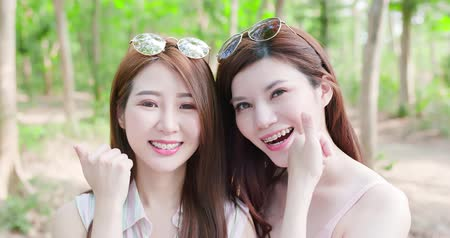 bestie : two beauty women wear brace and retainer for teeth show thumb up
