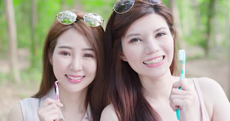 bracket : two beauty women wear brace and take interdental brush