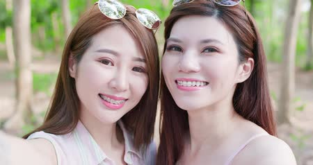 aparat ortodontyczny : two beauty women wear brace and retainer for teeth selfie happily
