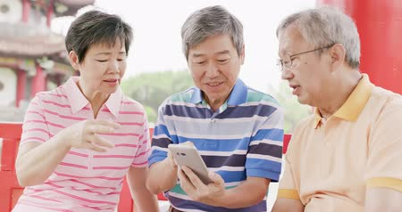 aposentar : old people sit in pavilion and use phone happily Stock Footage