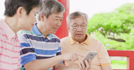 mobile game : old people sit in pavilion and use phone happily Stock Footage