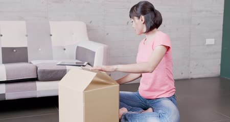 retailer : woman sit on the floor and packs things