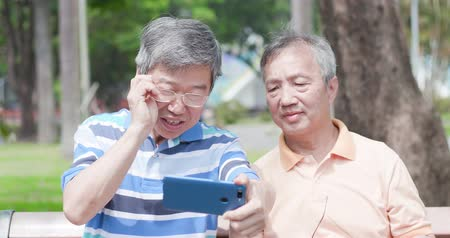 uśmiech : old man wear eyeglasses and look at phone in the park