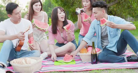 melão : people eat watermelon happily at a picnic
