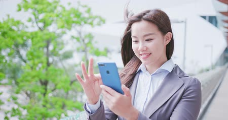 the city : business woman smiles happily and uses phone