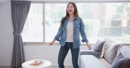 sofá : woman smiles happily and dances at home