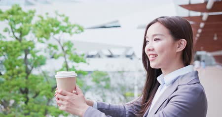 vision care : businesswoman holds coffee and look somewhere happily