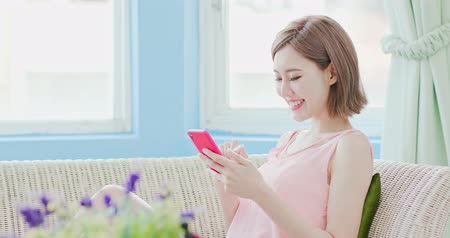 lakó : woman sits on sofa and uses phone happily at home Stock mozgókép