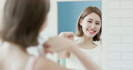 domy : woman choosing clothes and looks at mirror at home