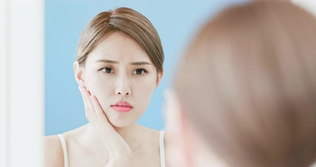 beauty spot : woman looking at mirror touches her face with acne problem