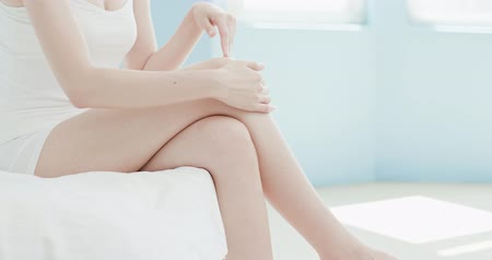 колено : beauty woman use cream with her leg at home Стоковые видеозаписи