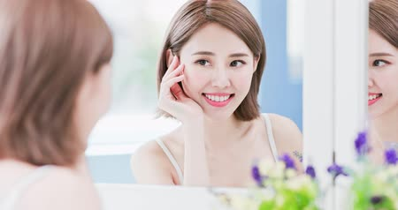 crows feet : beauty woman looking at mirror happily and touch her eye