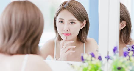 bochecha : beauty woman looking at mirror  and touches her face