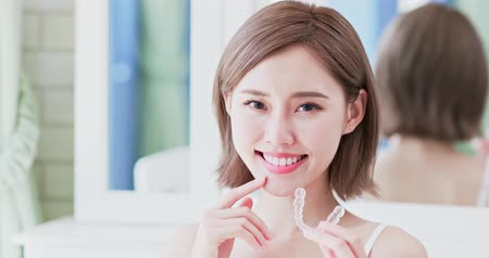 braces on teeth : close up of woman smiling happily and takes off invisible brace Stock Footage