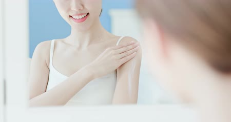fingers : beauty woman looks at mirror and applying cream on arm at home Stock Footage