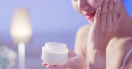 night : beauty woman apply cream with face on the bed at night Stock Footage