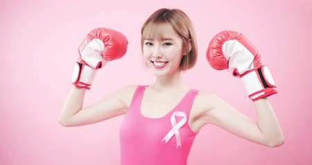 seio : woman wear pink ribbon and hold boxing gloves with prevention breast cancer concept Stock Footage